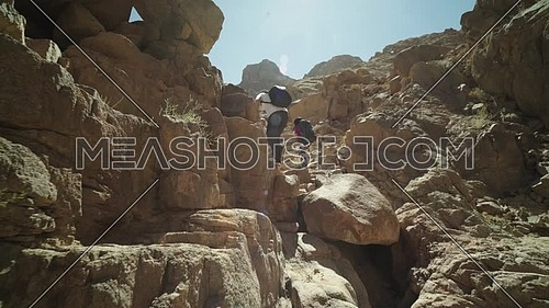 Track In shot for group of tourists climbing a big rocks to explore Sinai Mountain for wadi Freij at day.