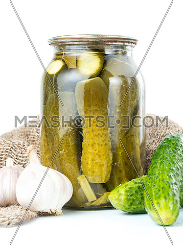 Pickled cucumbers isolated. Pickles in glass jar and garlic isolated on white background. Salted cucumber in jar isolated