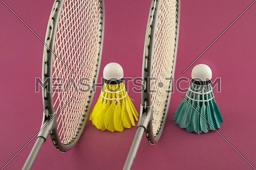 Badminton rackets and colorful feathered shuttlecocks in blue and yellow on punk background