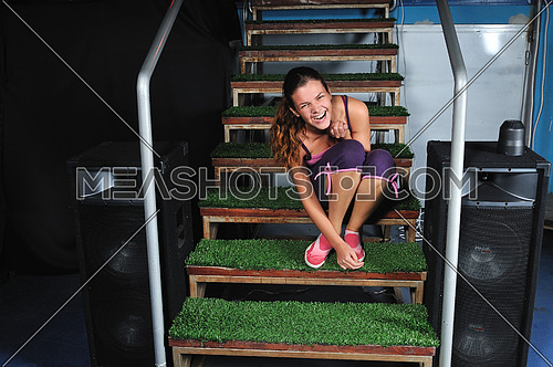 happy young woman smiling and seating on green stairs