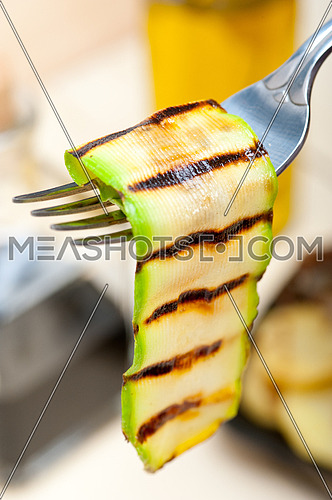 grilled zucchini courgette on a fork macro close up