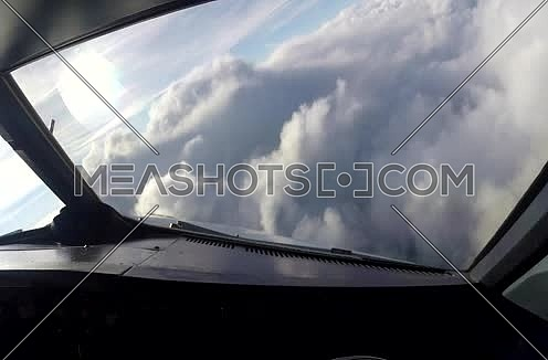 inside cockpit shot for plane flying over clouds