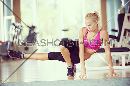 Cute young woman stretching and warming up for her training at a gym