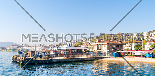 Istanbul, Turkey - April 27, 2017: Marmara Sea, Kinaliada Island Ferry Terminal with summer houses, and green mountains in the background
