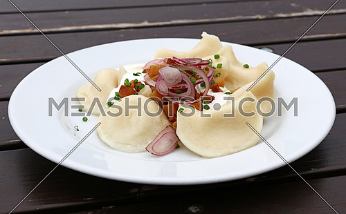 Plate of pierogi or varenyky stuffed filled dumplings with sour cream, bacon and onion, traditional East Europe cuisine meal popular in Poland, Ukraine, Slovakia and Russia, close up, low angle view