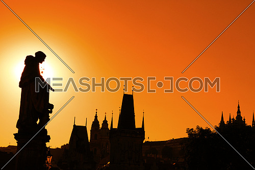 Sunset backlit silhouettes of statues and roofs of cityscape skyline at Charles Bridge in Prague, Czech Republic