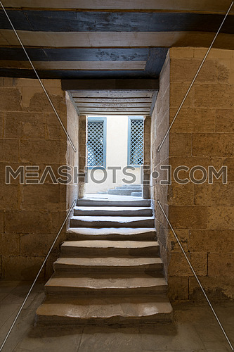 Aged narrow dark vaulted passage and staircase leading to outdoor small lobby with two yellow wooden windows, Mosque of Soliman Agha, Cairo, Egypt