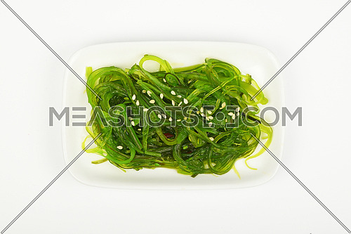 Portion of Asian traditional greed marinated seaweed salad appetizer on small white dish plate over white background, top view