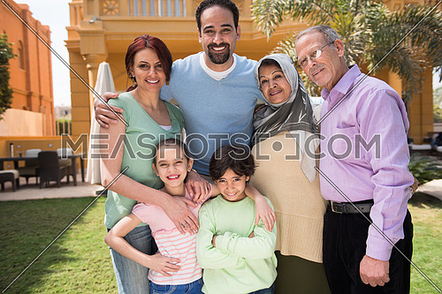 portrait of a happy middle eastern family in the yard of a beautiful sunny day