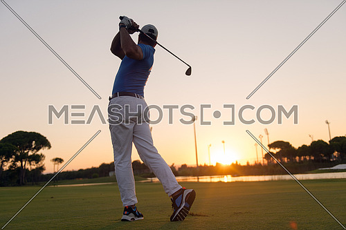 golfer hitting long shot with driver on course at beautiful sunset