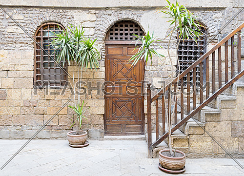 Facade of Beit El Set Waseela, showing a wooden closed door and two window with interleaved wooden grid and stair with wooden handrail, Medieval Cairo