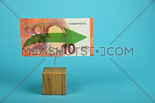 Stagnation and support of European economy and Euro currency, ten Euro banknote with green horizontal arrow on holder over blue background