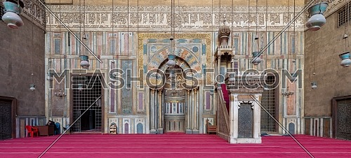 Cairo, Egypt - January 8 2019: Colorful decorated marble wall with engraved Mihrab (niche) and wooden Minbar (Platform) at the Mosque and Madrassa (School) of Sultan Hassan
