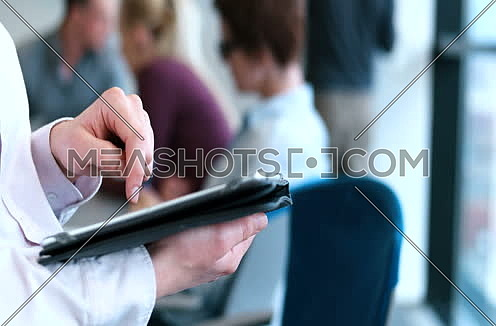 Close up hands businesswoman using touch screen tablet in modern office building