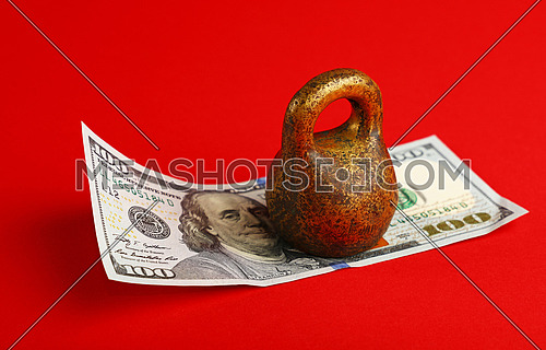 Close up one hundred US dollar paper currency banknote under pressure of heavy vintage metal weight over red background with copy space, high angle view