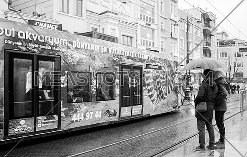 Couple under the rain in front of a tram