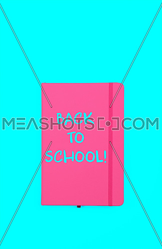 Back to school handwritten sign on pink leather cover notebook over blue paper background with copy space