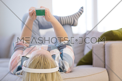 Young beautiful girl enjoying music through headphones, laying on sofa at home