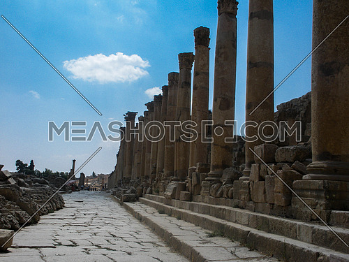 An old Roman path in an historical Archaeological site with huge stones poles in Jordan