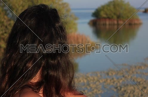Close-up shot for a girl setting on the sea shore looking towards an Island with green trees at wadi Lahmi at day - 5D