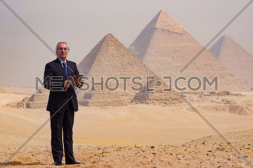 mature arab business man using tablet computer in desert with great giza pyramids in background