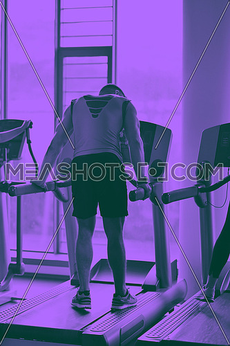 Handsome man running on the treadmill in modern gym duo tone