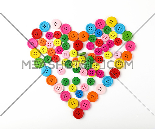 Heart shaped of colorful multicolor round painted wooden handmade sewing buttons isolated on white, close up, elevated top view