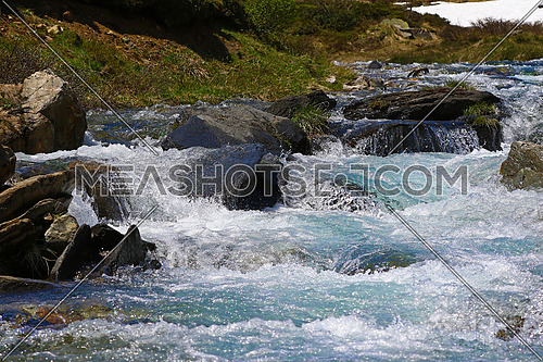 Clear mountain water running from a glacier to a dam