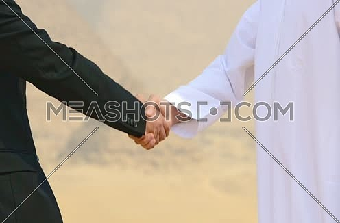 close up successful emiratie and egyptian business men at pyramids shaking hands