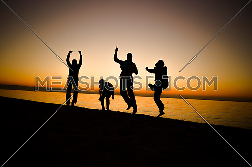 four friends having fun at the beach by sunset