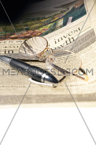 pen and glassesand newspaper over white glass table