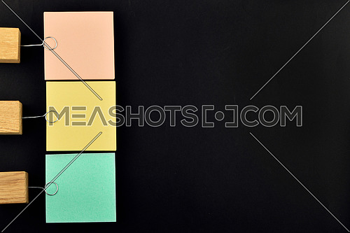 List, three paper notes, green, yellow, pink, with wooden holder isolated on black paper background for presentation