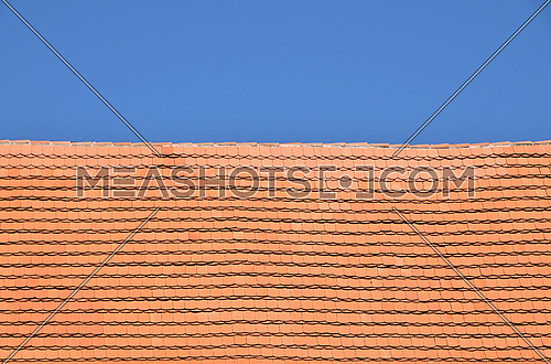 Traditional red brown ceramic roof tiles pattern over background of clear blue sky, close up, low angle side view