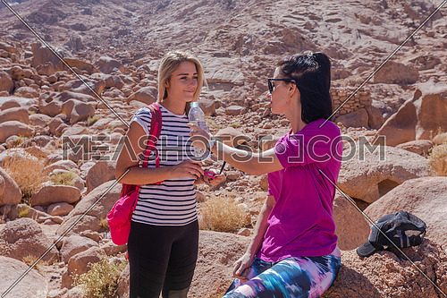 Long shot for two female tourists exploring at Sinai Mountain for wadi Freij by day.