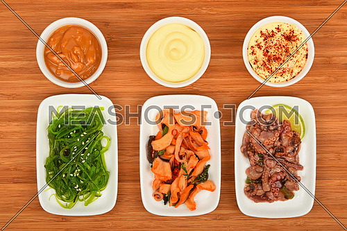 Three portions of seafood marinated salad with octopus cuttlefish, squid and seaweeds in small white plates with sauce on wooden table, top view