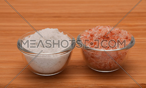 Choose your salt - Himalayan or rock salt (side view) on wooden bamboo background