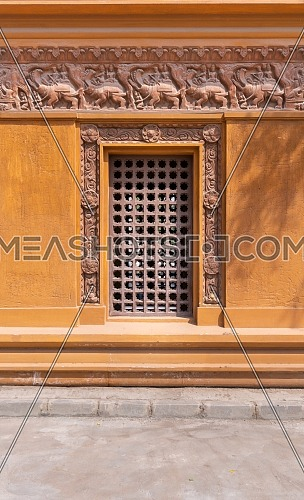 Wooden grid window installed in ornamental wall outside of old stone building, Baron Empain Palace, Heliopolis, Cairo, Egypt