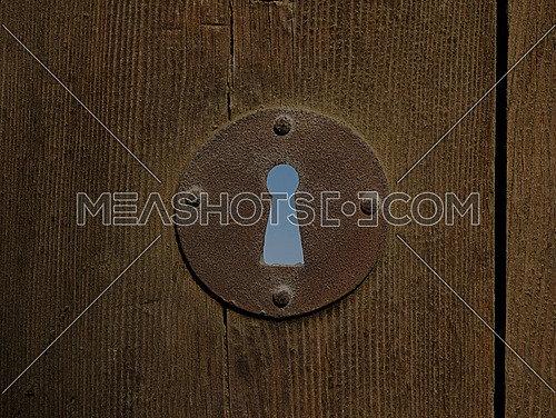 A rusted keyhole of an aged wooden door, revealing the sky