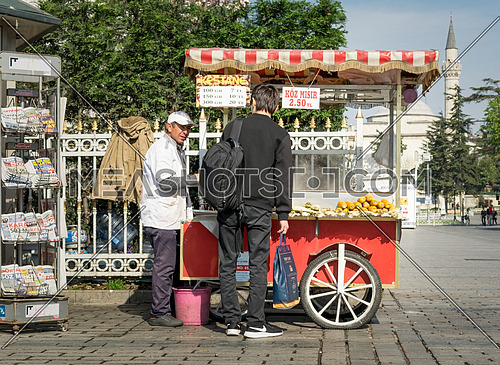 Istanbul, Turkey - April 16, 2017: Tourist buying fast food meal from a traditional Turkish chestnut and corn cart in Sultan Ahmed Square