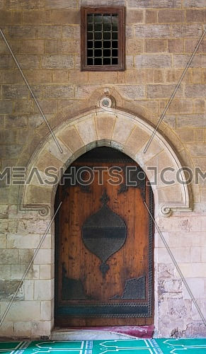 Vaulted closed decorated wooden grunge door in bricks stone wall at public historic Al Moaayad Mosque, Cairo, Egypt