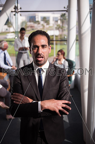 Portrait of a male executive wearing eye glasses and a group meeting is taking place at the background in a bright office