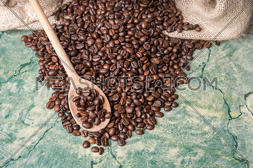 Coffee beans in coffee burlap bag on green table and wooden spoon with coffee beans on top,view from above.