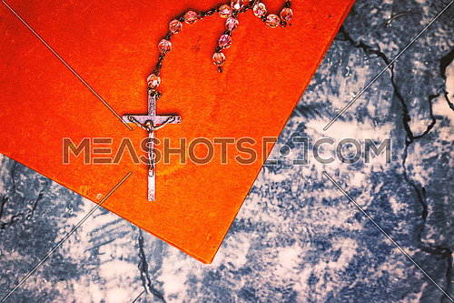 Silver rosary and cross resting on the closed book at gray table, seen from above.religion school concept.Vintage style.