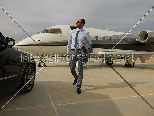 Portrait of a young successful middle eastern businessman at the airport in front of his private plane