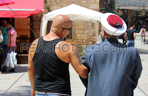 islamic Sheikh and a tattooed man hand in hand 20 august 2015