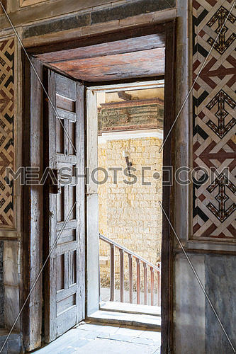 Angled view of a wooden aged ornate opened door leading to a passage with bright light, color decorated marble wall, and marble floor at historic public mosque of Sultan Qalawun, Cairo, Egypt