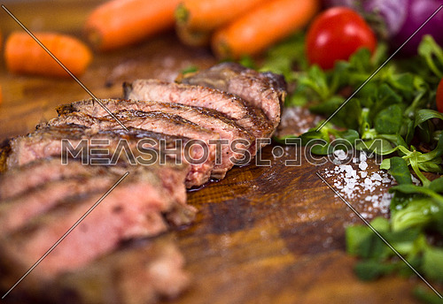 Juicy slices of grilled steak  with vegetables around on a wooden board