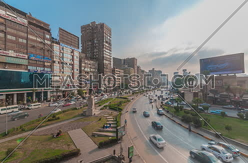fixed shot for traffic in Gamet Al Dowal Street Showing Naguib Mahfouz Statue at Cairo at Day