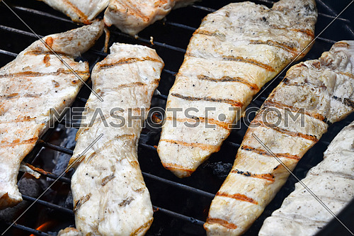 Chicken or turkey meat barbecue steak ready cooked grilled on bbq smoke round grill, close up