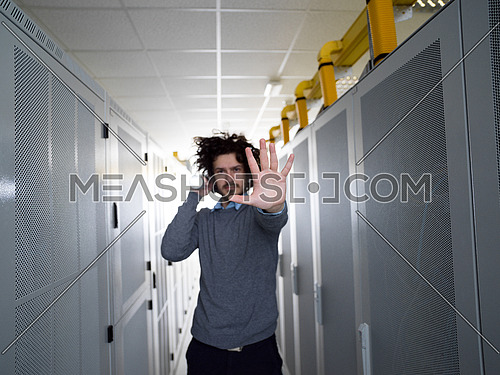 Young IT Technician shining light on server at the data center